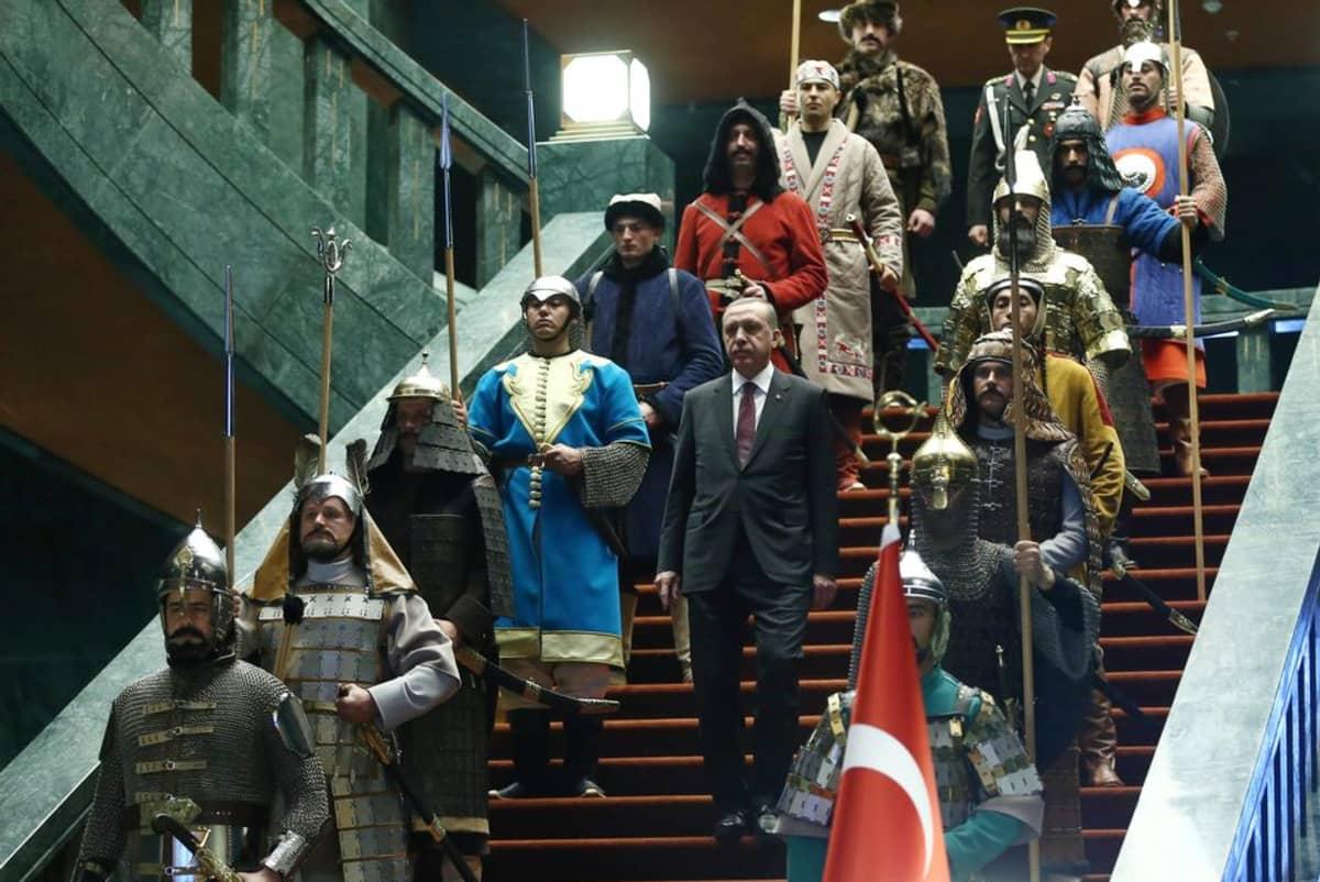 Presidentti Erdogan rappusissa uudessa palatsissaan. Ympärillä naamiaisasuihin puettuja ritareita.