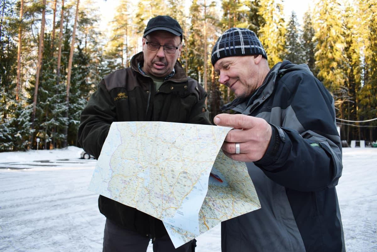 Kaksi miestä katsoo karttaa.