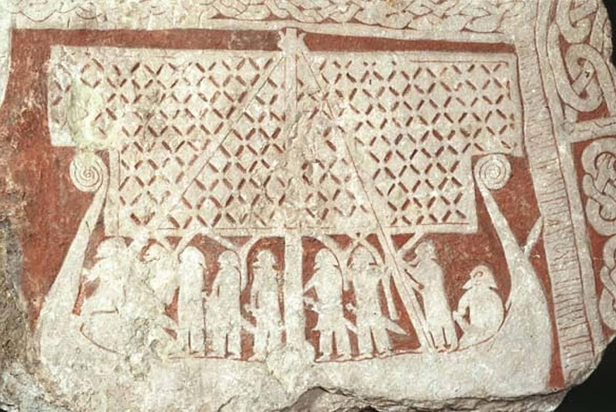 Kiveen kaiverrettu purjelaiva, jossa kahdeksan miekkamiestä sekä peräsimenpitäjä.