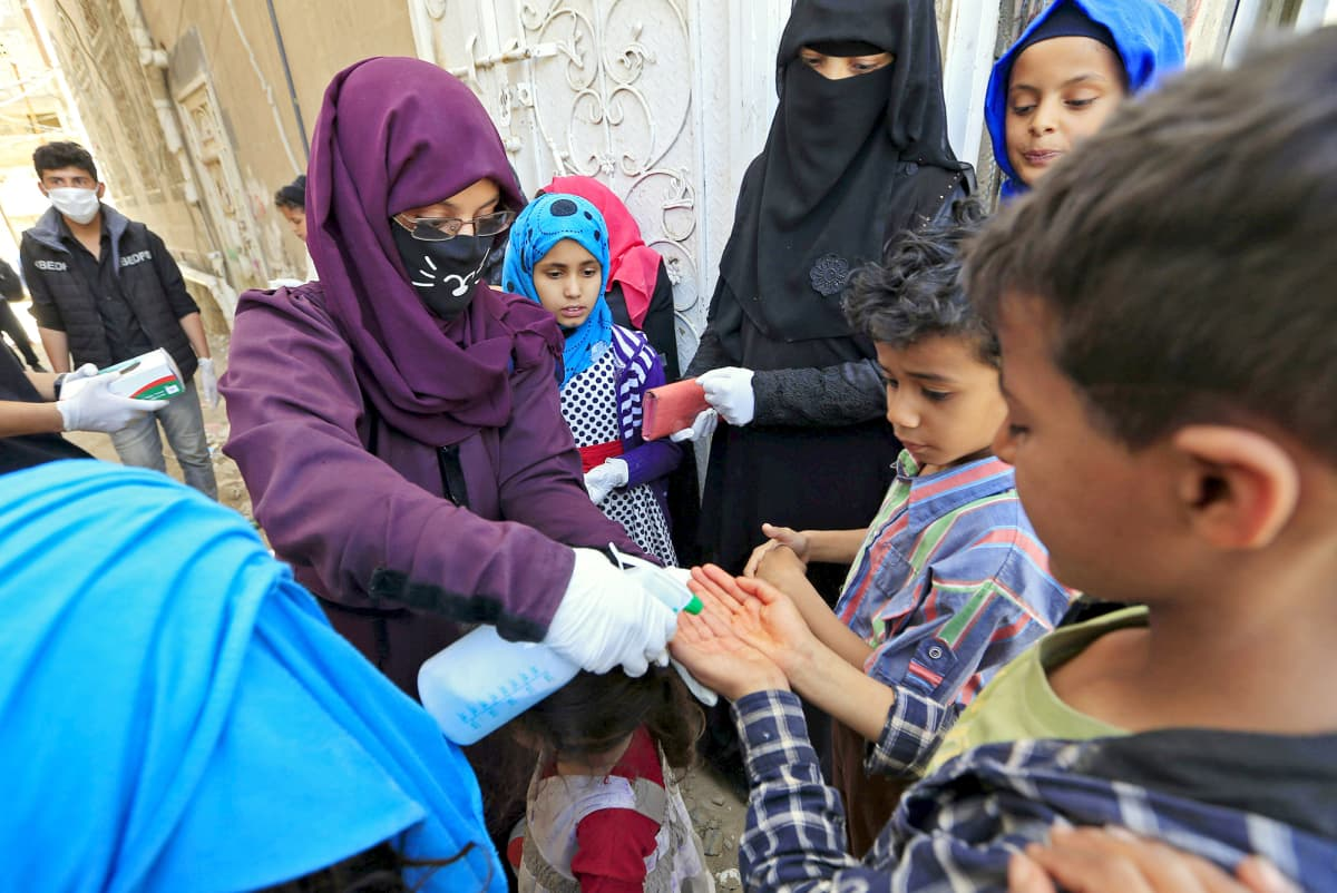 Vapaaehtoistyöntekijä desinfioi lasten käsiä kadulla Sanaassa.