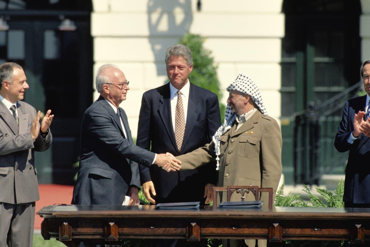 Washington D.C vuonna 1993, tuolloiset Israelin pääministeri Yitzhak Rabin, Yhdysvaltain presidentti Bill Clinton ja Palestiinan vapautusjärjestön puheenjohtaja Yasser Arafat sopimassa Oslon sopimuksesta.