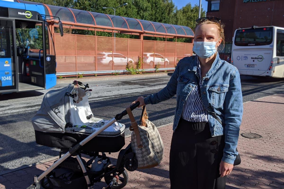 Katri Saukkonen lastenrattaiden kanssa ja maski naamalla.