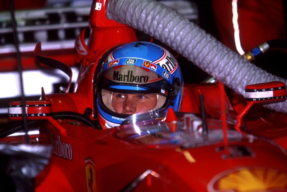 Mika Salo istuu Ferrarin F1-autossa kypärä päässä.