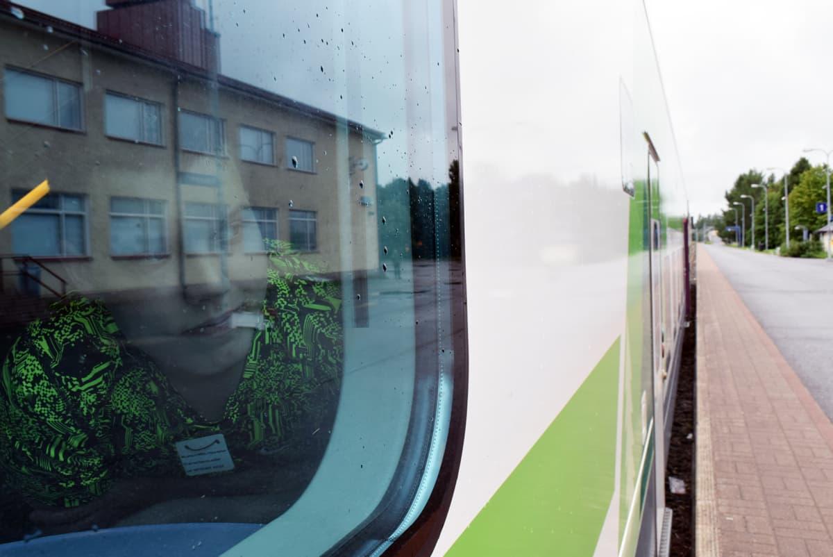 Matkustaja kurkistaa junan ikkunasta rovaniemen asemalla.