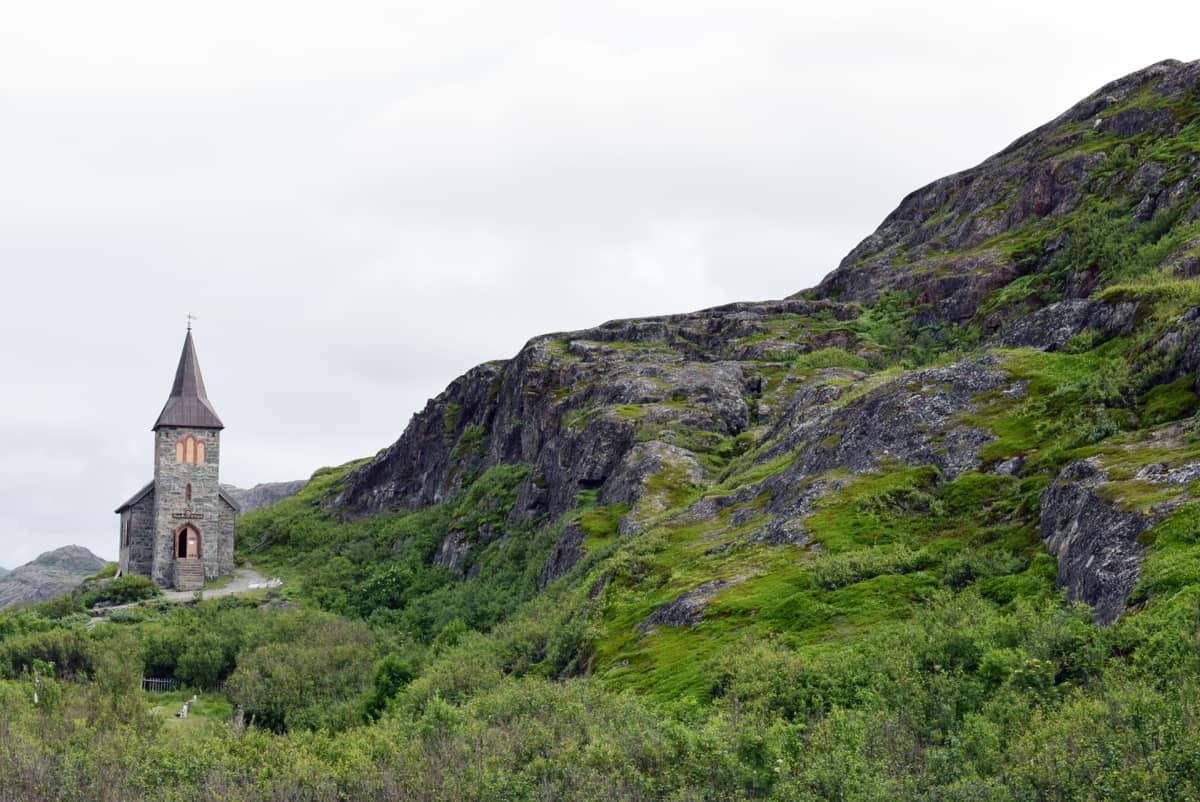 Kirkko kallioisessa maastossa tuntureiden välissä.