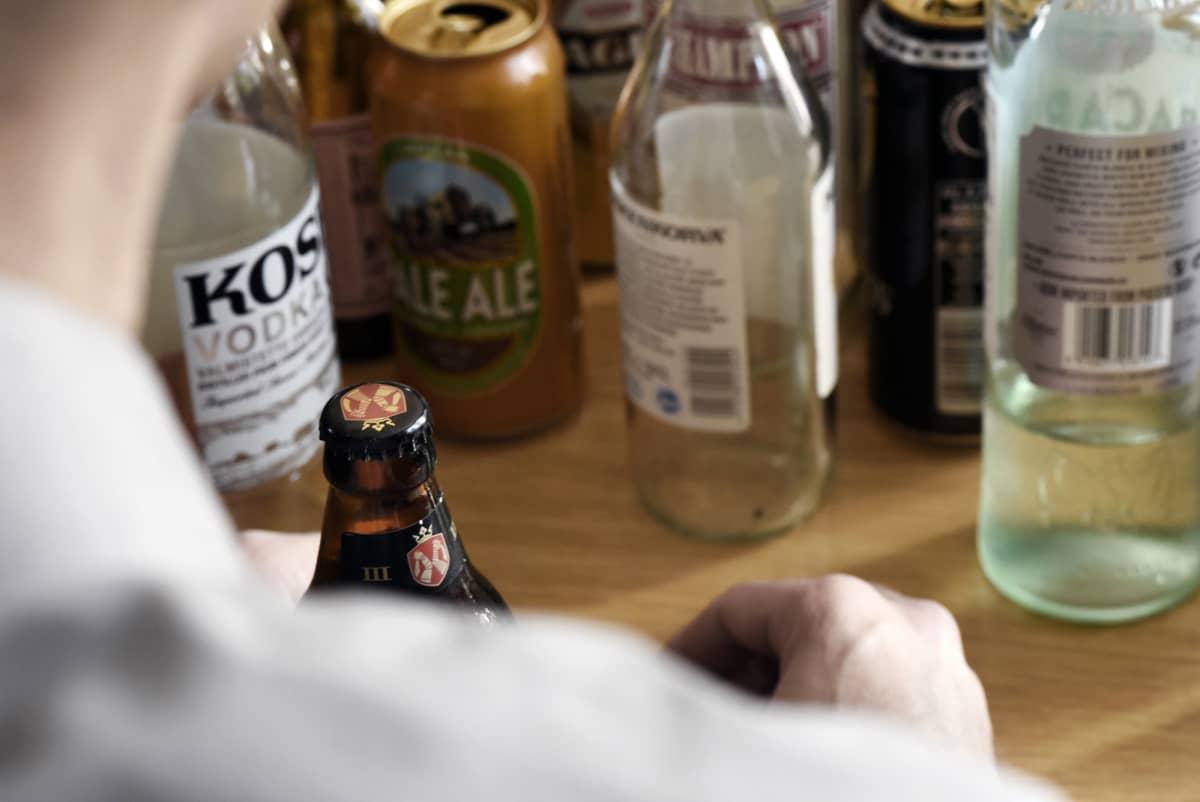 Mies istuu pöydän ääressä edessään olutta ja viinaa.