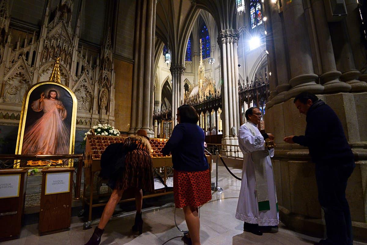Ihmiset sytyttävät kynttilöitä ja vastaanottavat ehtoollista pääsiäissunnuntaina katedraalissa New Yorkissa.