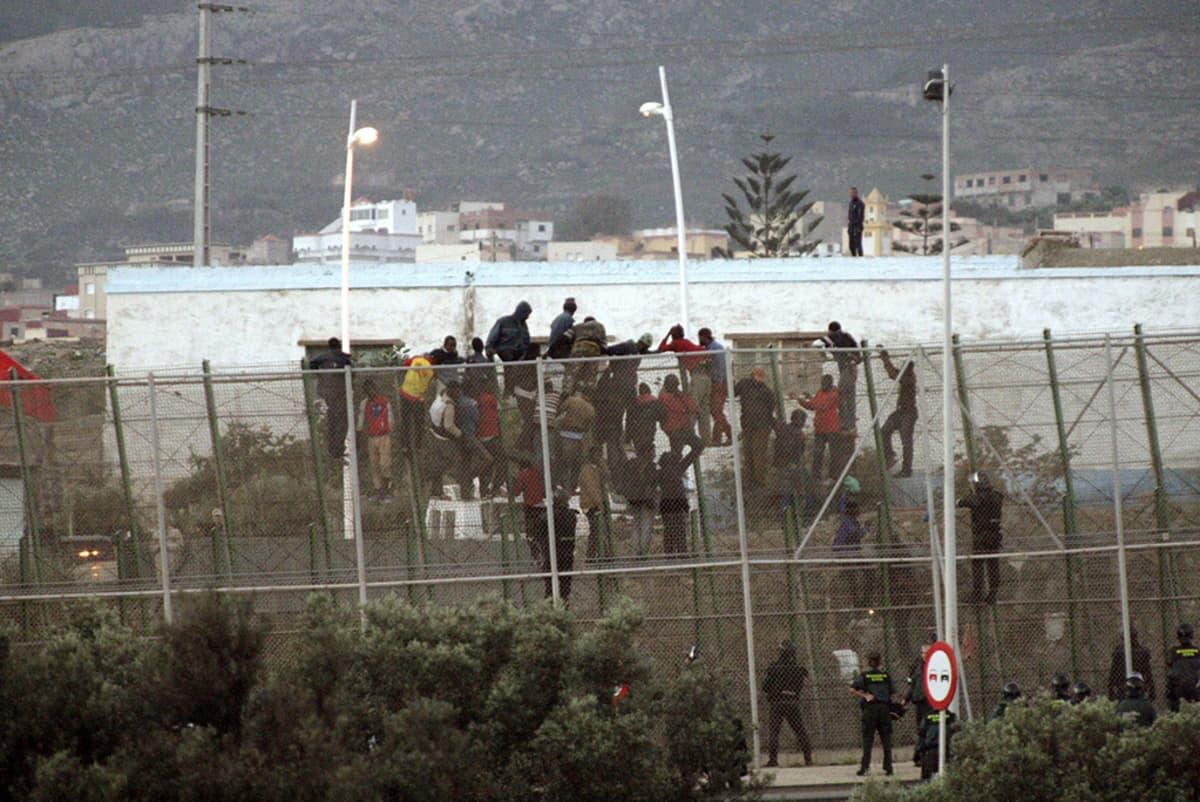 Siirtolaisia ylittämäässä aitaa Marokon rajalla Melillassa 31. lokakuuta 2014.