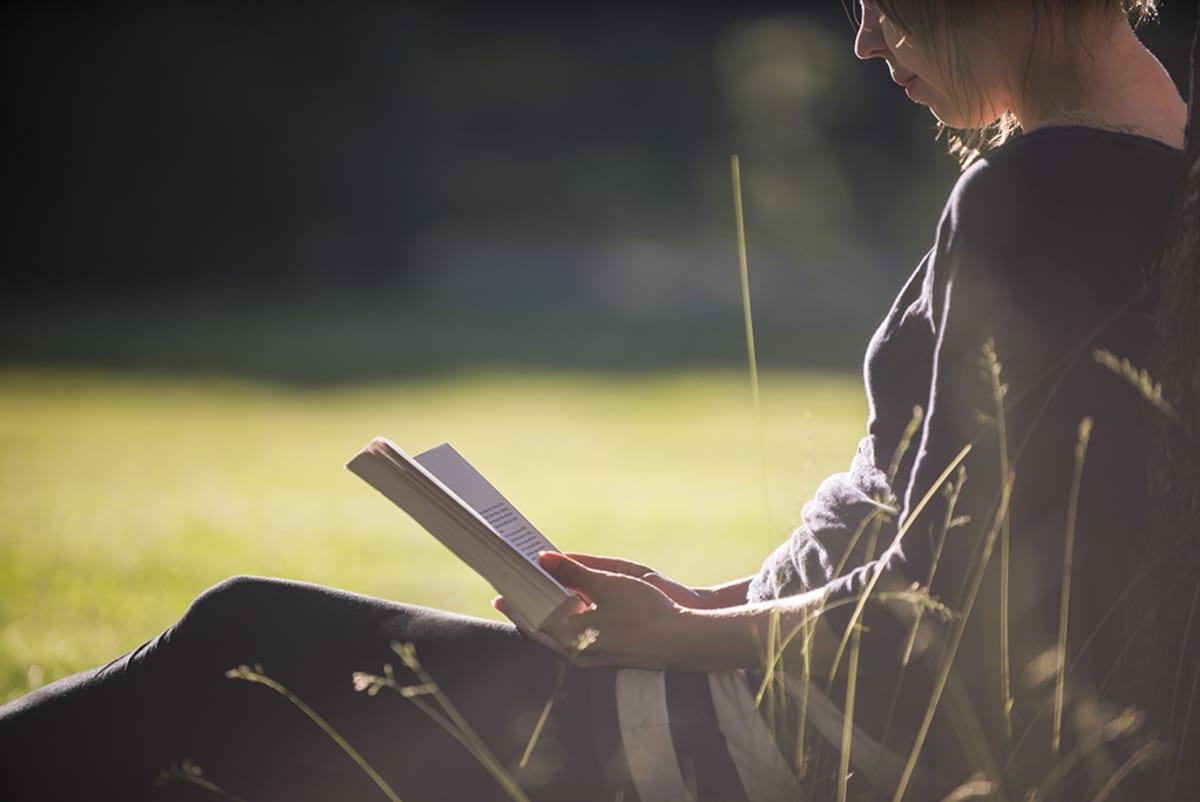 Nainen lukee kirjaa luonnossa.