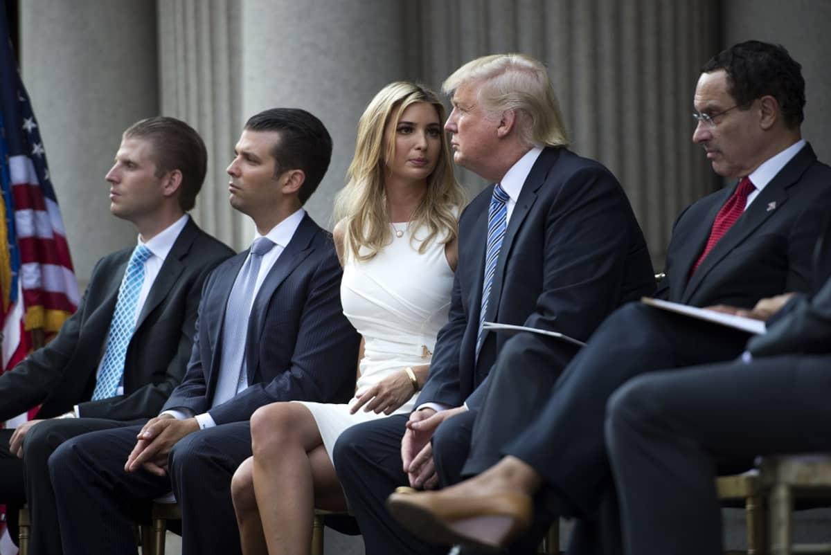 Koko perhe istuu rinnakkain. Ivanka ja Donald keskustelevat keskenään.