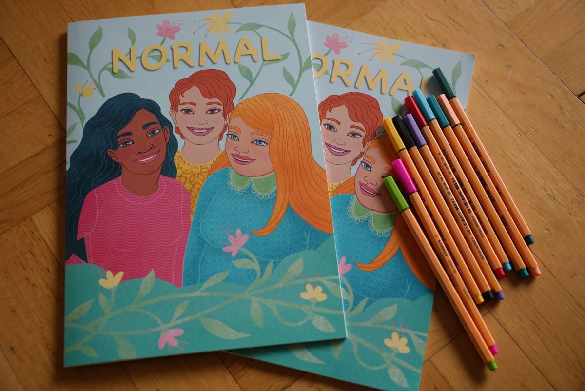 värityskirja, jonka nimi on Normal, kannessa nuorten piirrettyjä kuvia ja vieressä kyniä
