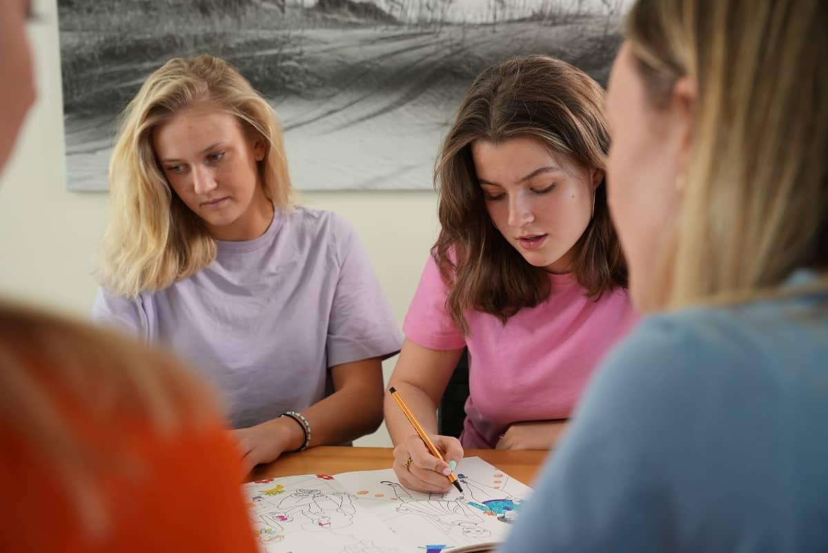neljä nuorta naista värittää värityskirjaa