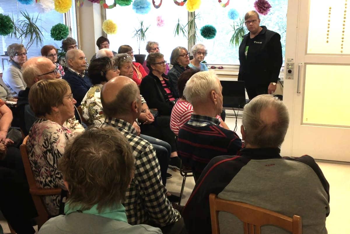 Mies puhuu ihmisille, jotka istuvat kuuntelemassa Urjalassa.