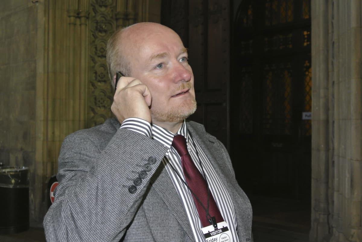 Päätoimittaja Arto Henriksson puhuu kännykkään.