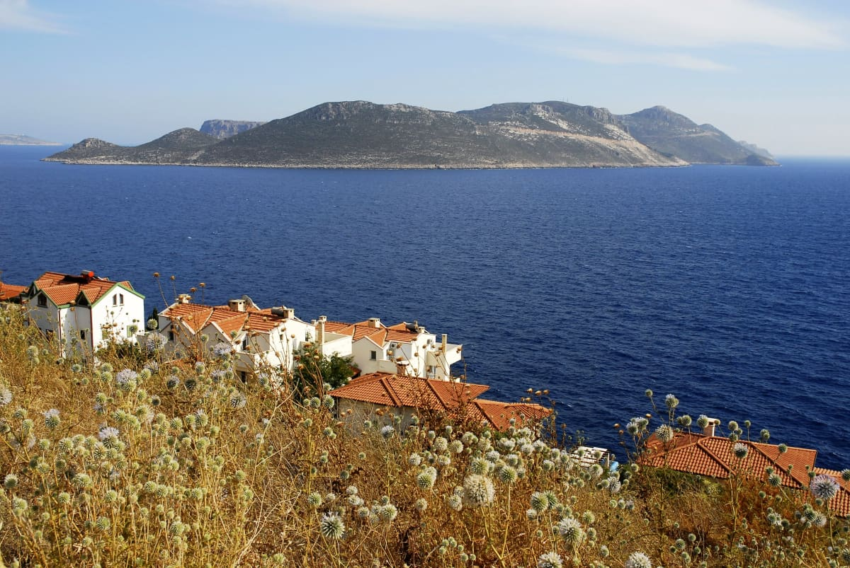 Maisema Turkin rannikolta kohti Kastellorizon saarta. Etualalla on taloja. Saari on keskellä sinisenä loistavaa merta.