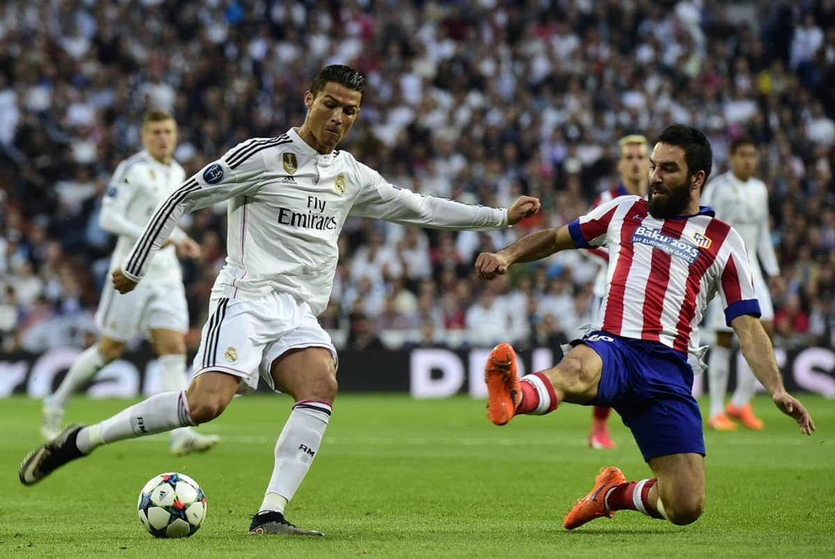 Real Madridin Cristiano Ronaldo laukoo ja Atletico Madridin Arda Turan peittää.