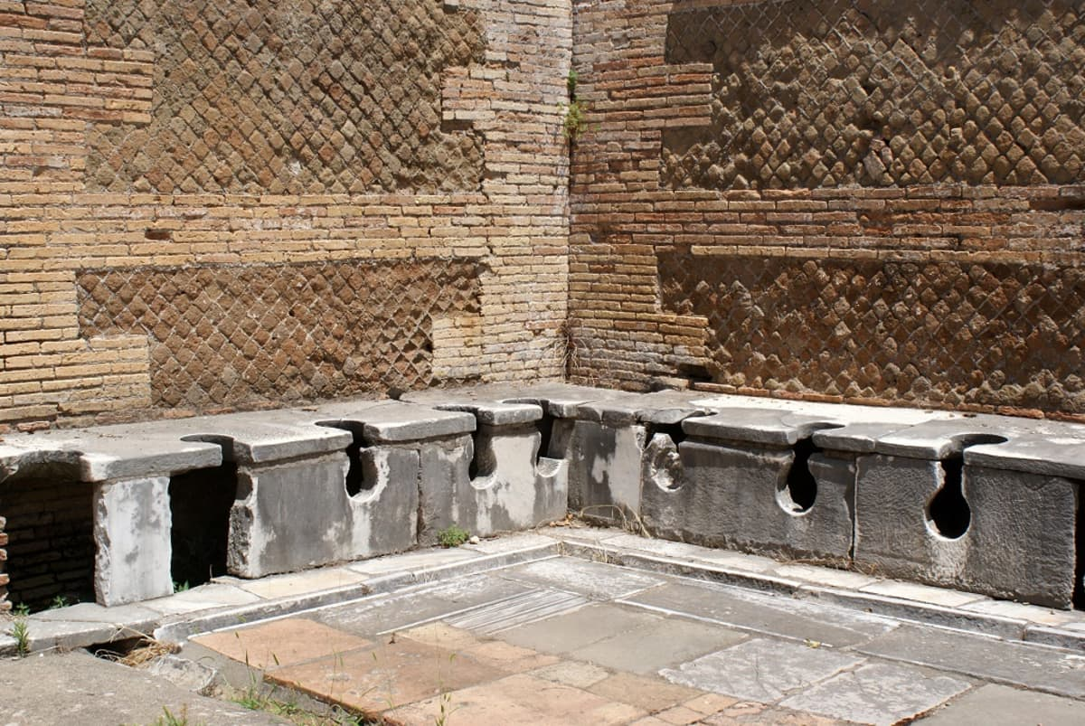 Tiilistä rakennetun huoneen kulma, jossa kummallakin seinällä on kiviset penkit ja niissä vieri vieressä käymälän reikiä.