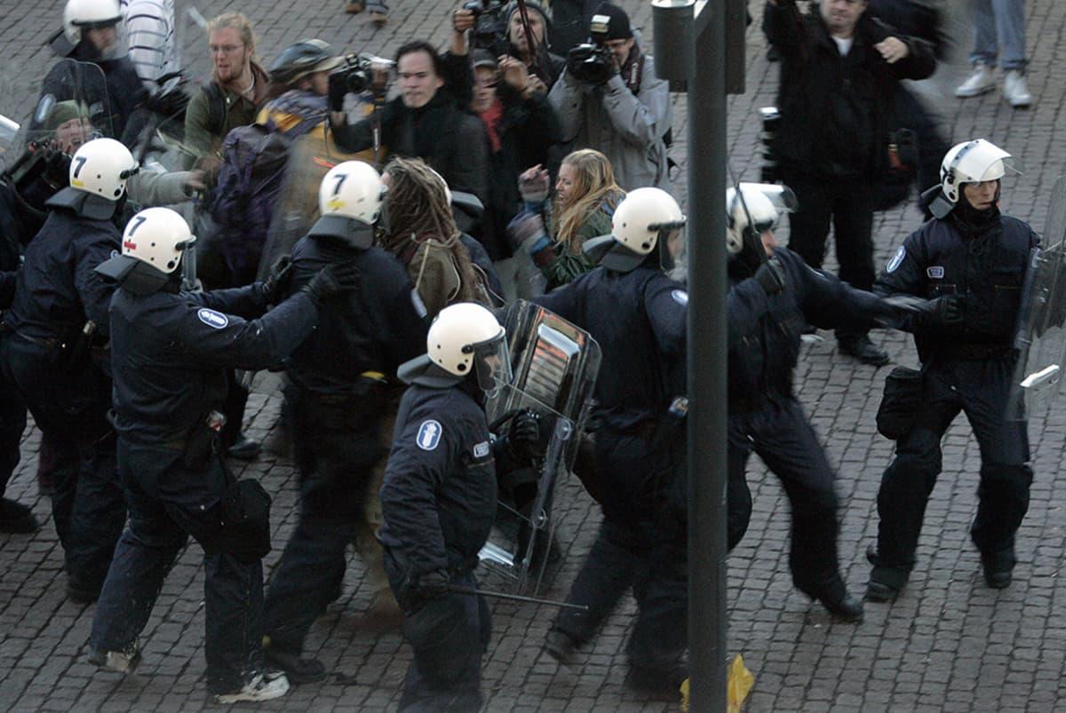 Poliiseja ja mielenosoittajia Smash Asem -mielenosoituksen aikana Kiasman edustalla Helsingissä.