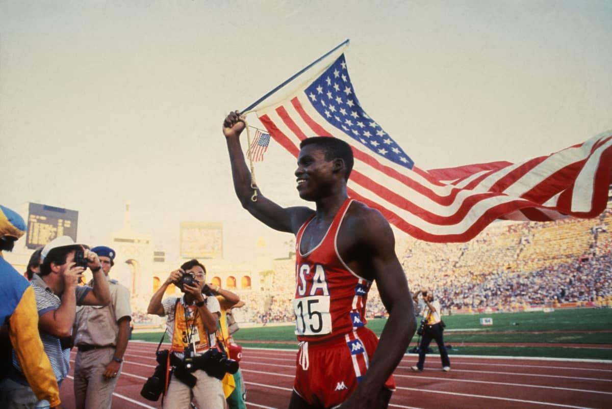 Carl Lewis heiluttaa Yhdysvaltain lippua.