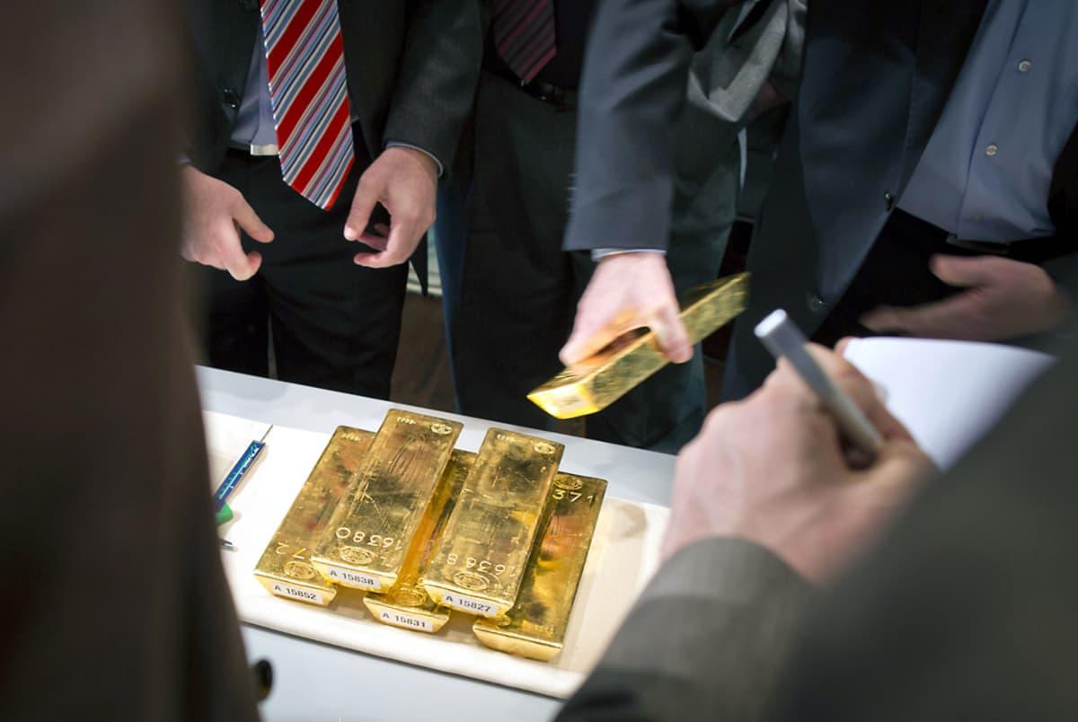 Kultaharkot ovat pinossa pöydällä ja niitä esitellään puvut päällä oleville toimittajille.
