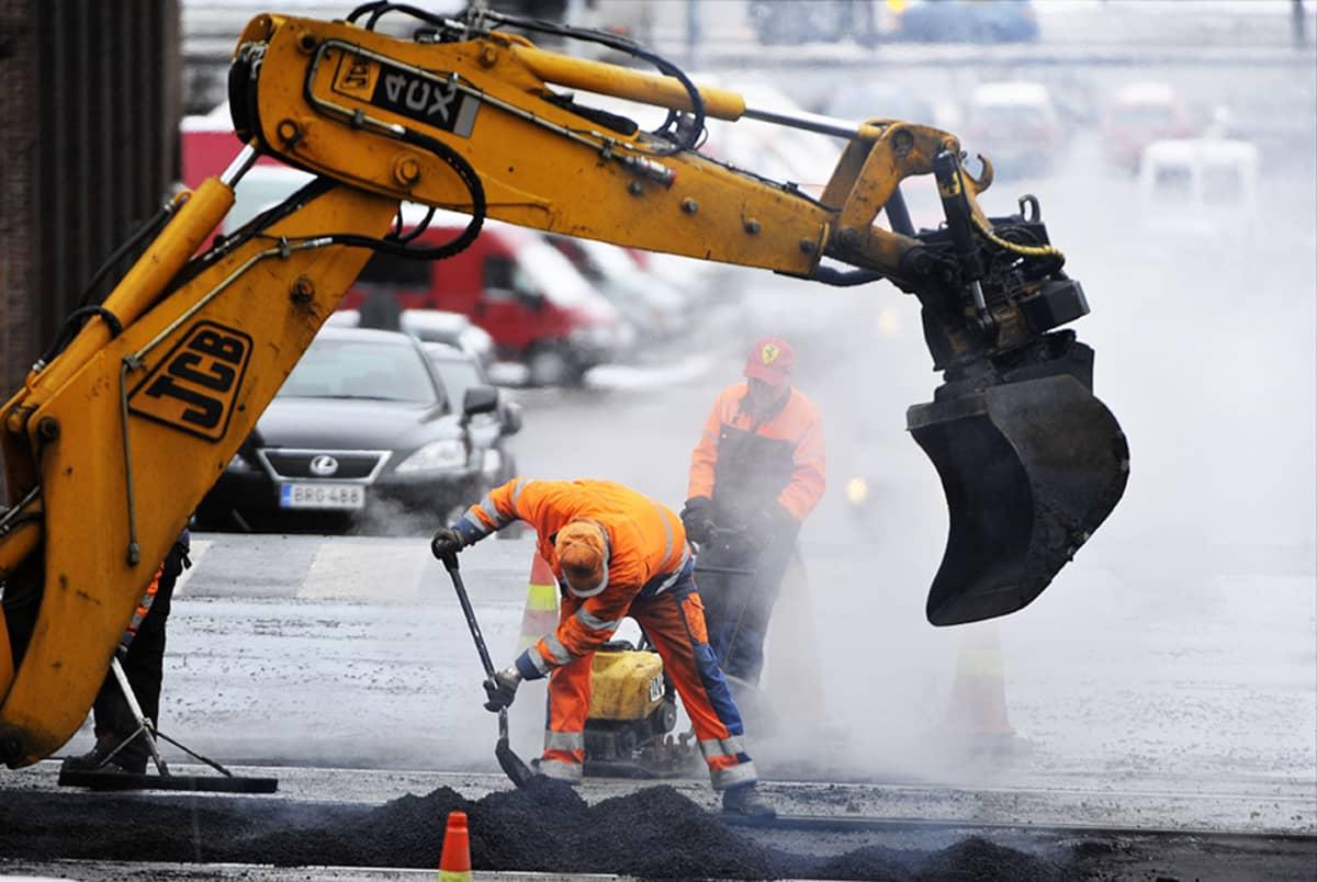 Tietyöläisiä työstämässä asfalttia.