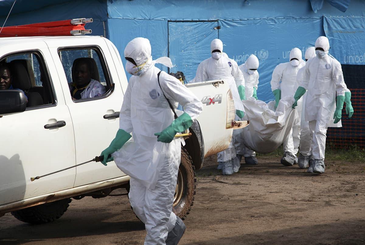 Työntekijät kantoivat ebolaan kuollutta naista haudattavaksi Foyan kaupungissa, Liberiassa 2. heinäkuuta.