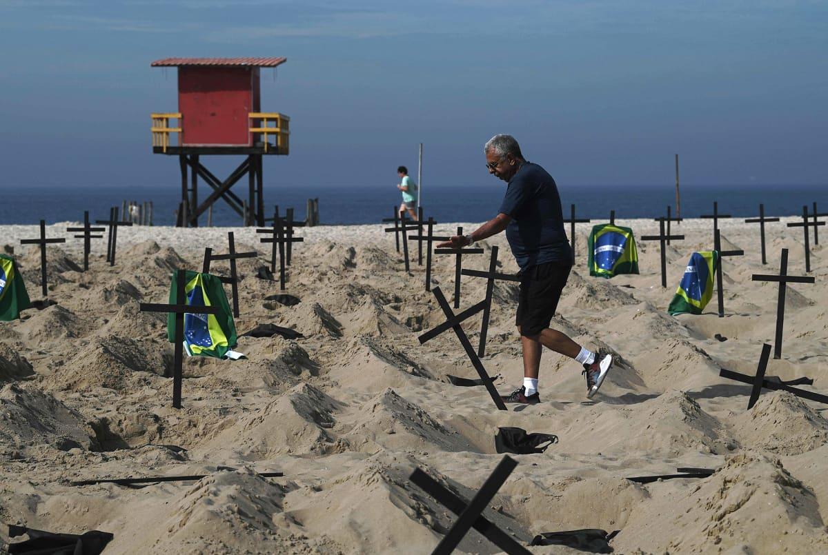 Mies kaatamassa rannalle pystytettyjä ristejä.