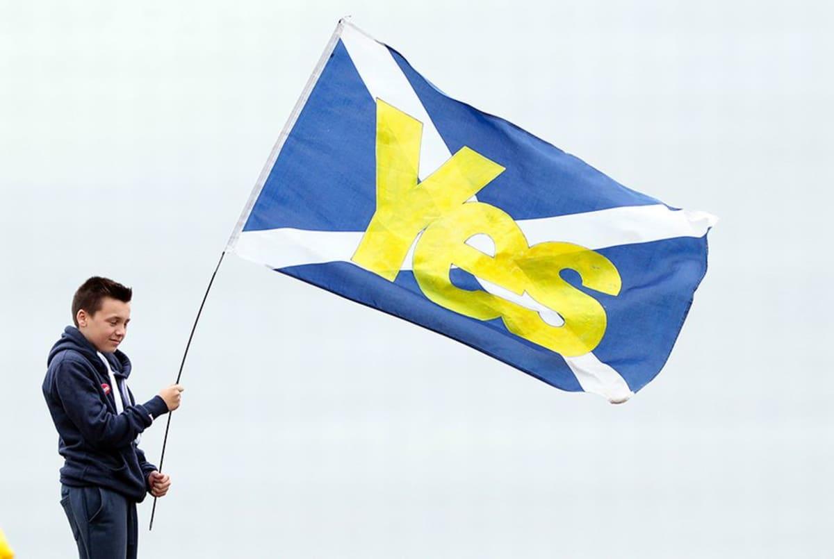"""Poika pitelee Skotlannin lippua, jossa lukee """"Kyllä""""."""