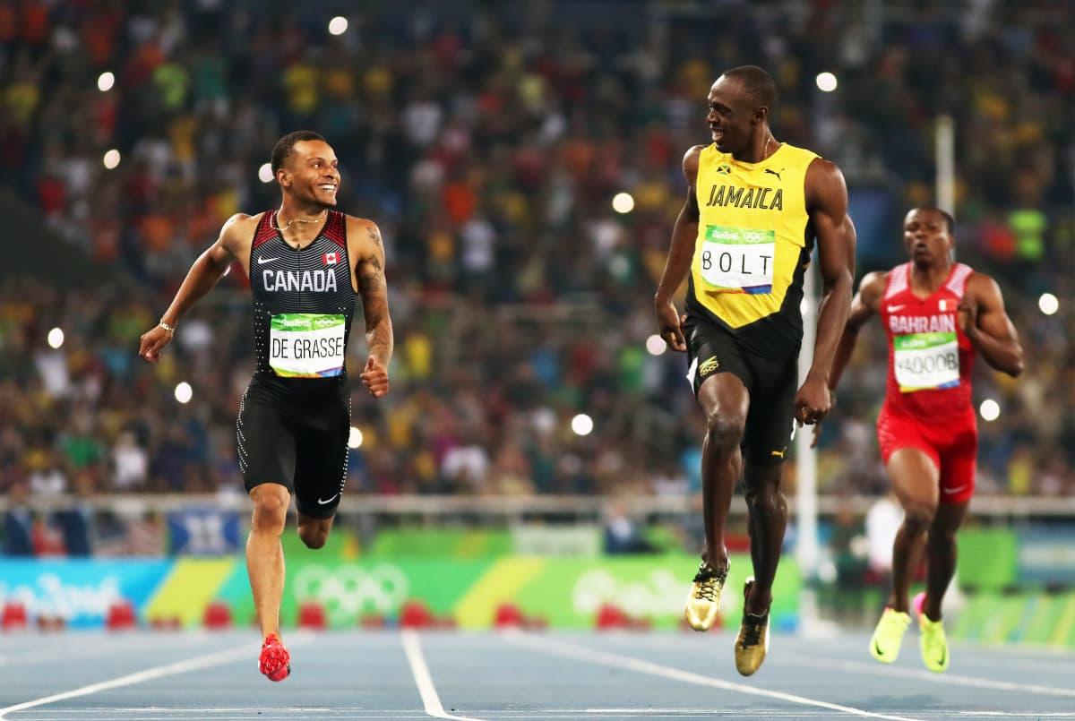 Andre De Grasse (vas.) ja Usain Bolt hymyilevät toisilleen maaliviivan ylittämisen jälkeen.