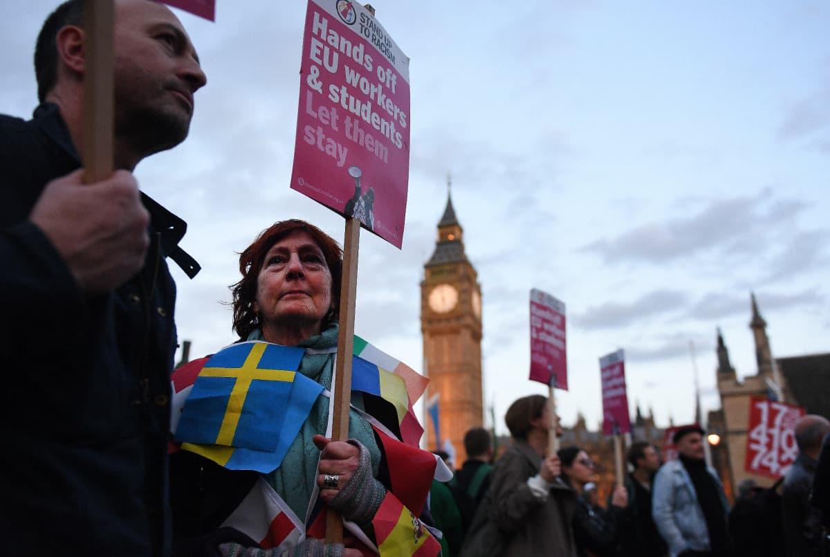 Mies ja nainen mieltä osoittavan väkijoukon edessä Lontoossa parlamenttitalon edustalla. Naisella kyltti, jossa vaaditaan EU-kansalaisille oikeutta jäädä maahan sekä eri EU-maiden liput kaulansa ympärillä.