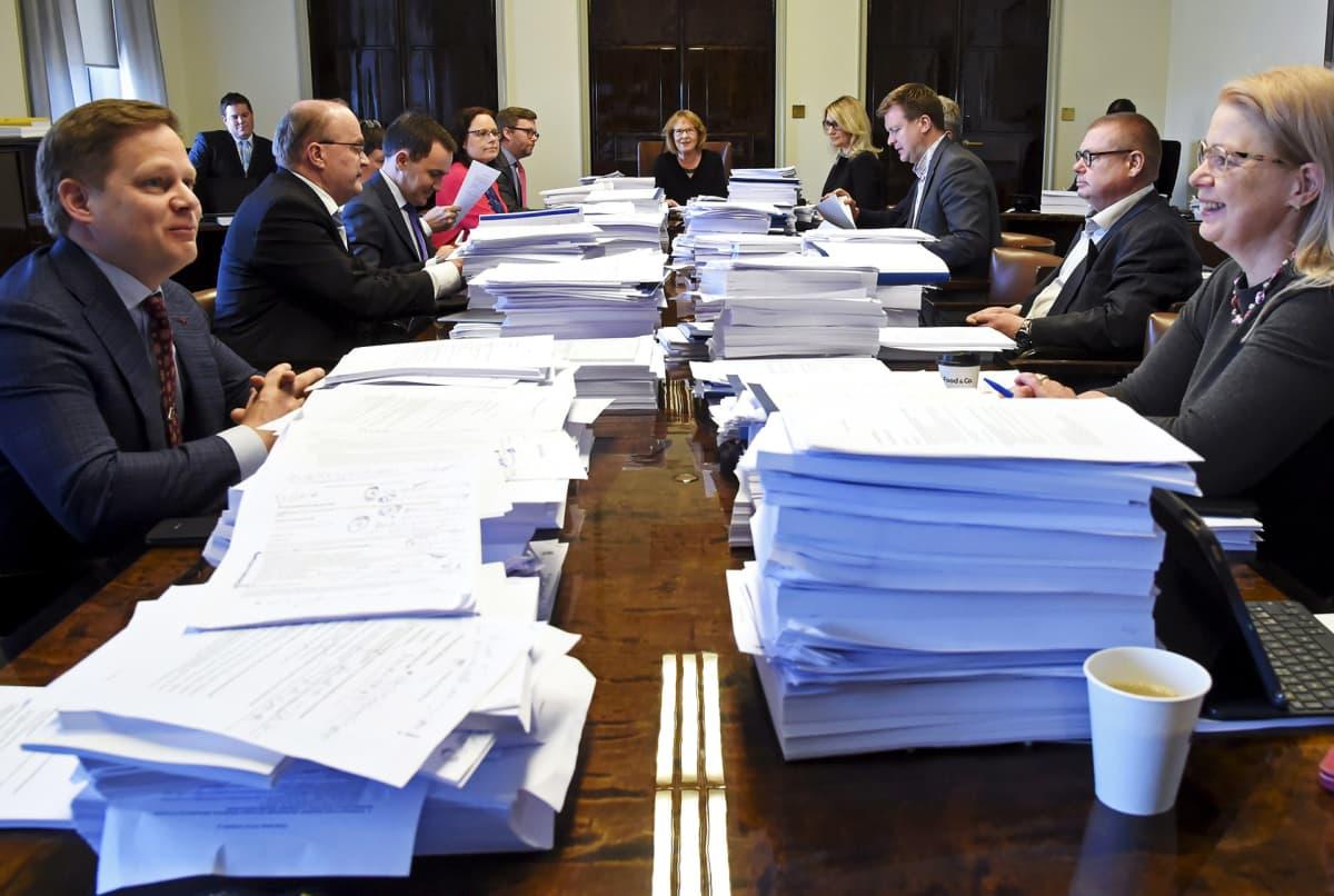 Perustuslakivaliokunta kokoontuneena suurien paperipinojen äärelle.
