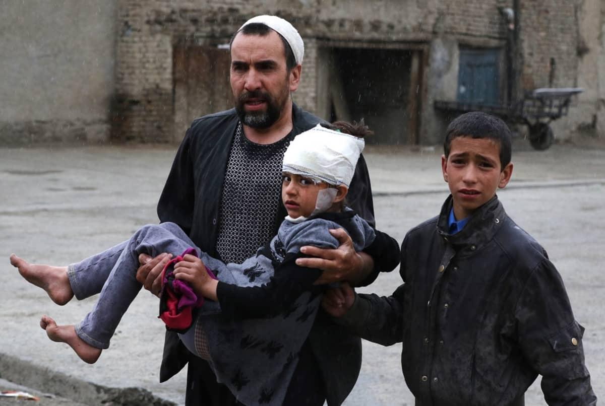 Mies kantaa sylissään pommi-iskussa haavoittunutta tyttöä.