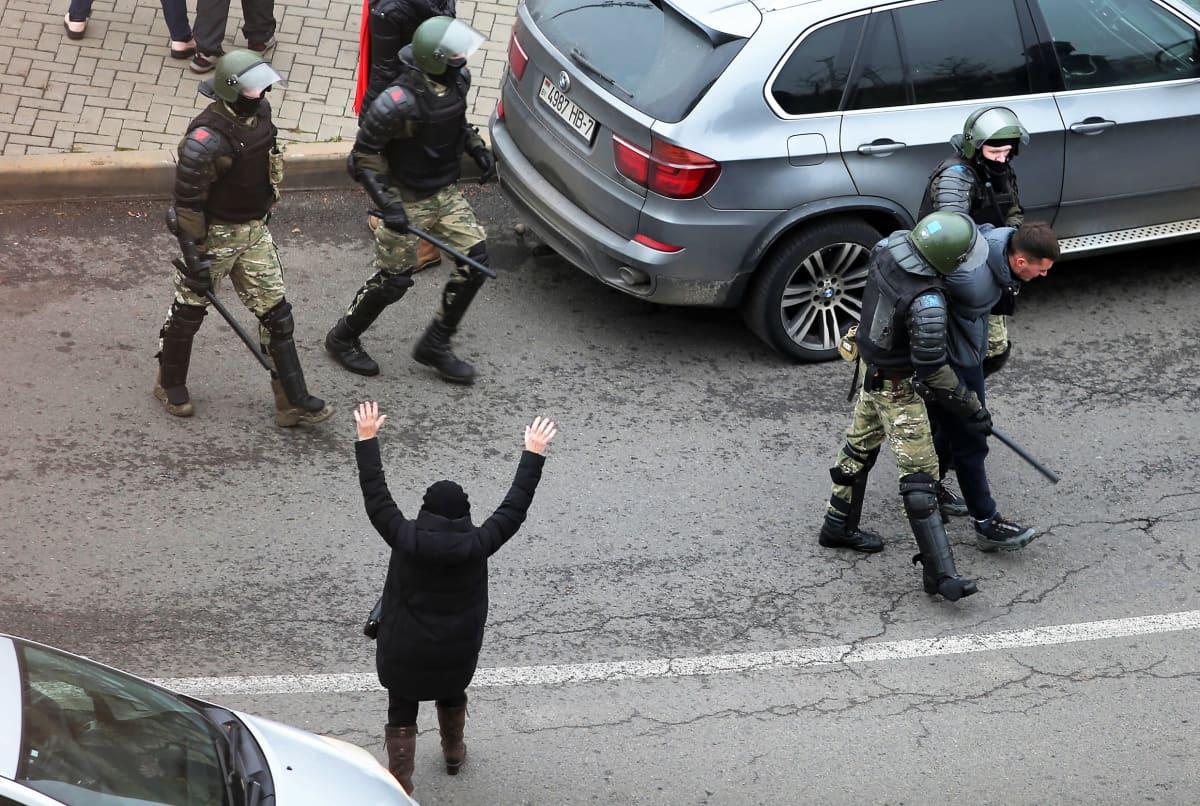 Kaksi mellakkavarusteista poliisia kuljettaa pidättämäänsä miestä keskellään kadulla. Taaemapana tulee kaksi mellakkapoliisia puolijuoksua. Mustapukuinen ihminen pitää käsiään ylhäällä kuin yrittäen kiinnittää heidän huomiotaan..