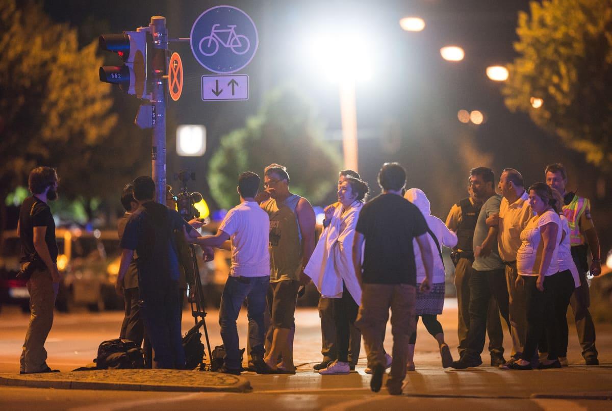 Ihmisiä ostoskeskuksen läheisyydessä Münchenissä ammuskelua seuranneena yönä 23. heinäkuuta.