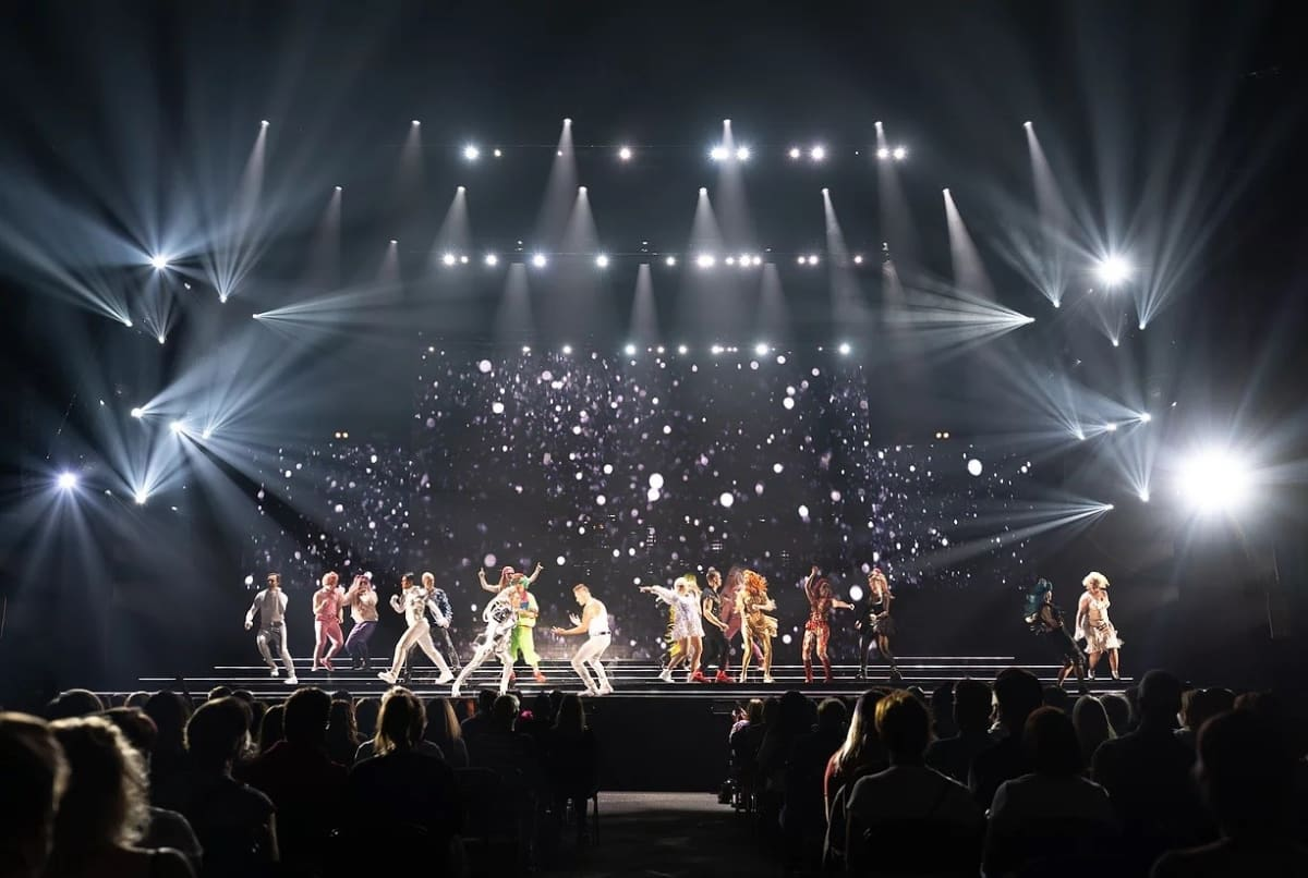 Tanssijoita hämärällä lavalla. Yllä kirkkaat valot.
