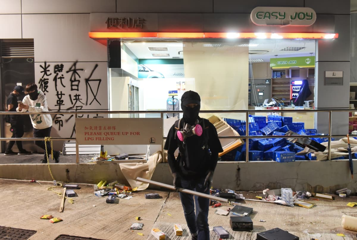 Mielenosoittaja vandalisoidun liiketilan edessä Kowloon Tongin alueella Hongkongissa 14. marraskuuta.