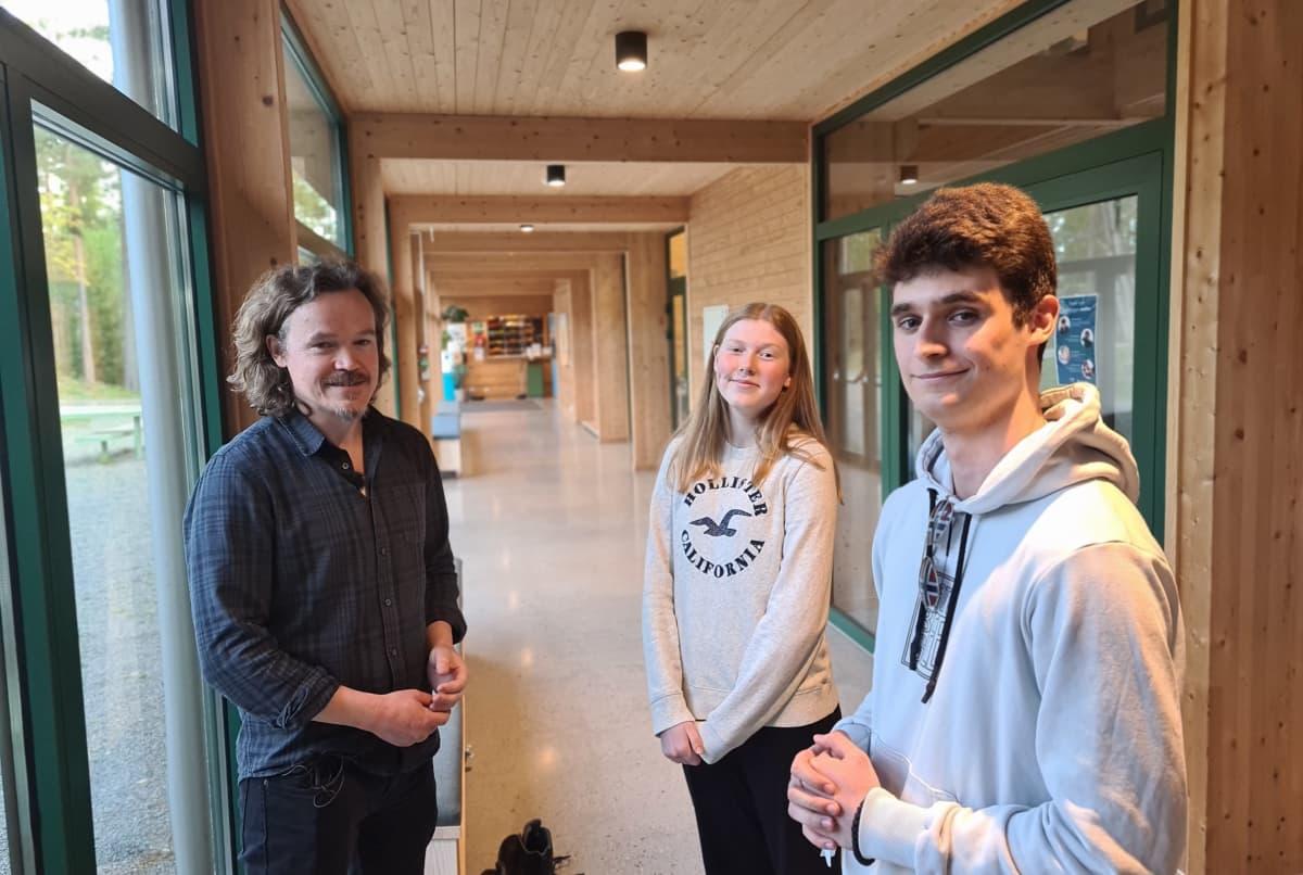 kaksi nuorta ja kurssin ohjaaja katsovat kameraan hymyillen