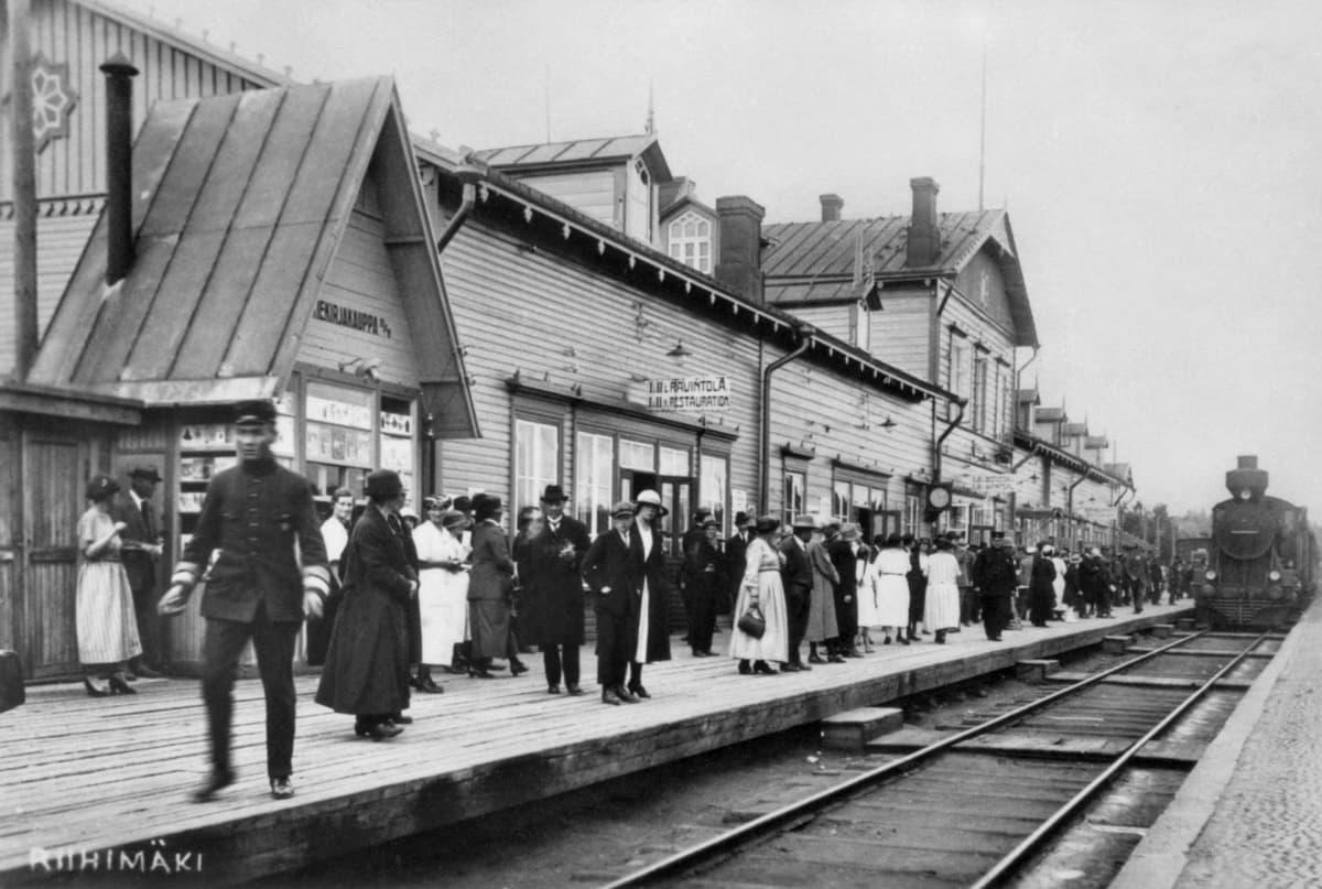 Riihimäen rautatieasema. Asemalaituri, jossa matkustajat odottavat juuri saapuvaa junaa.