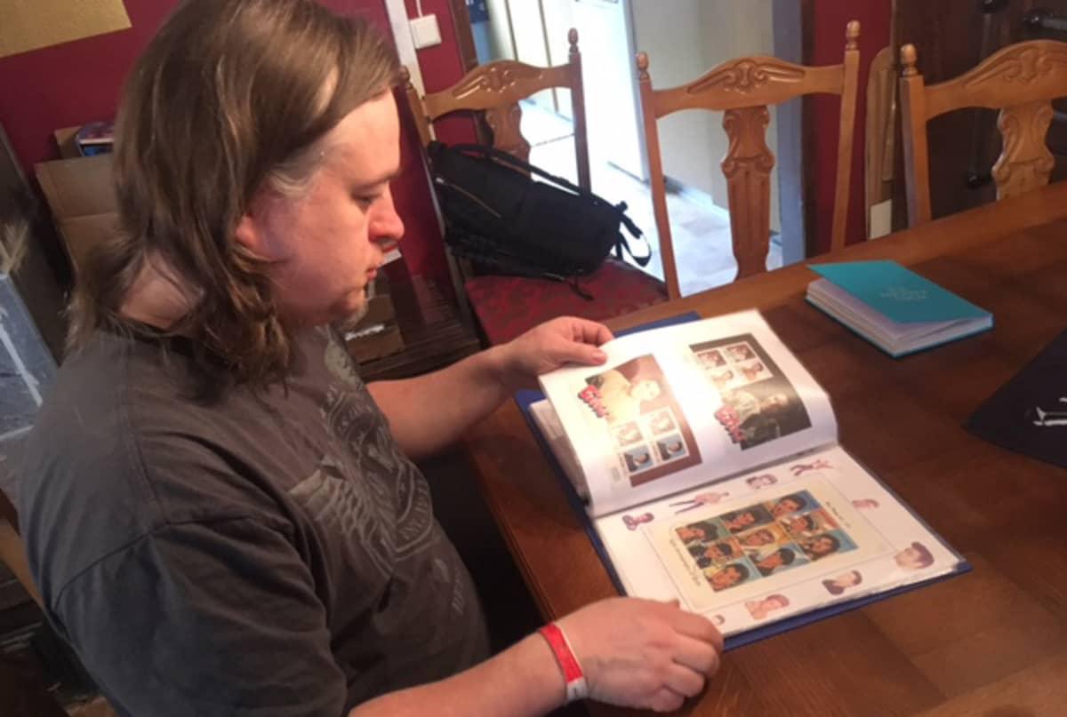 Tomi Raussi selaa Elvis-postimerkkikokoelmaa