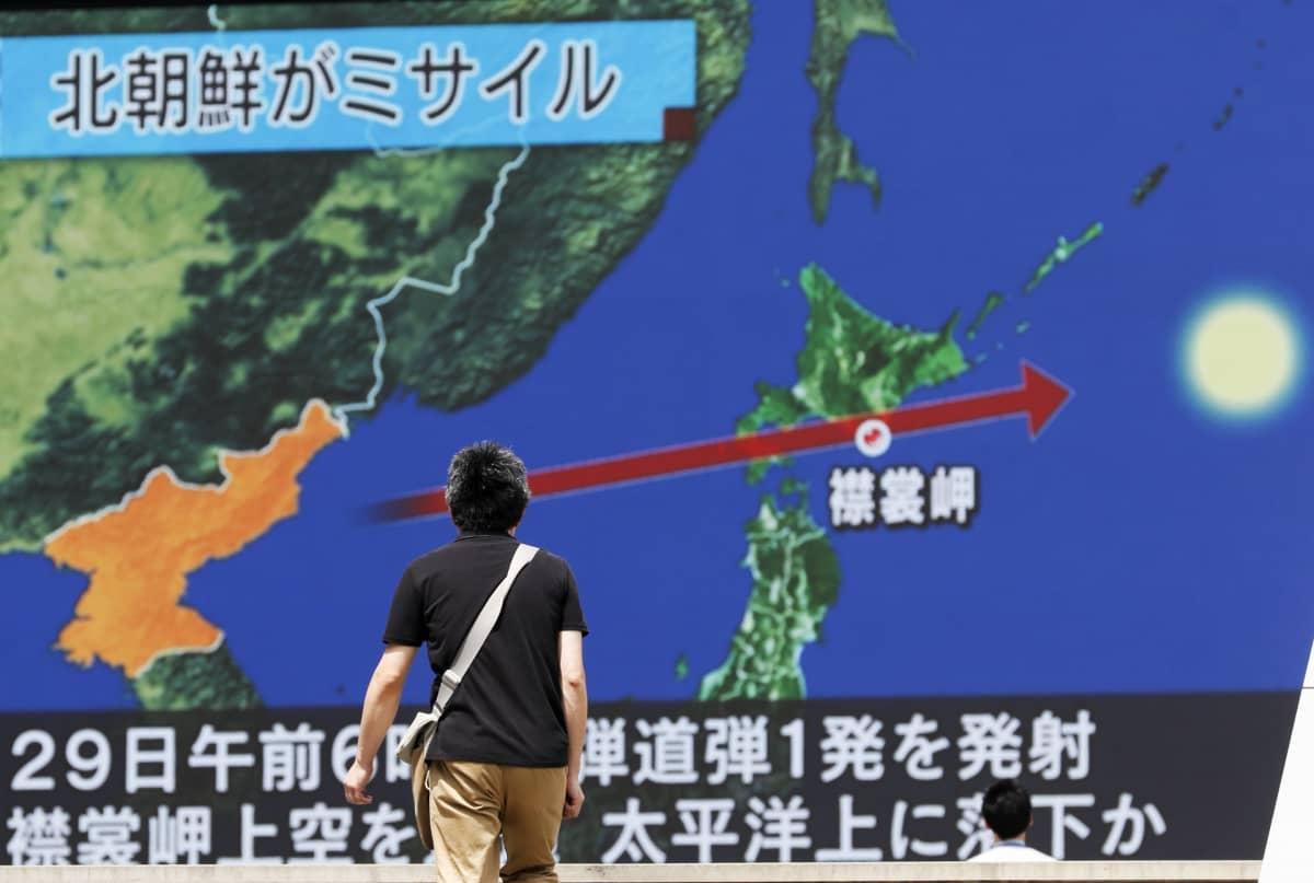 Mies katselee suurta näyttöä, jossa näkyvään karttaan on merkitty ohjuksen reitti.