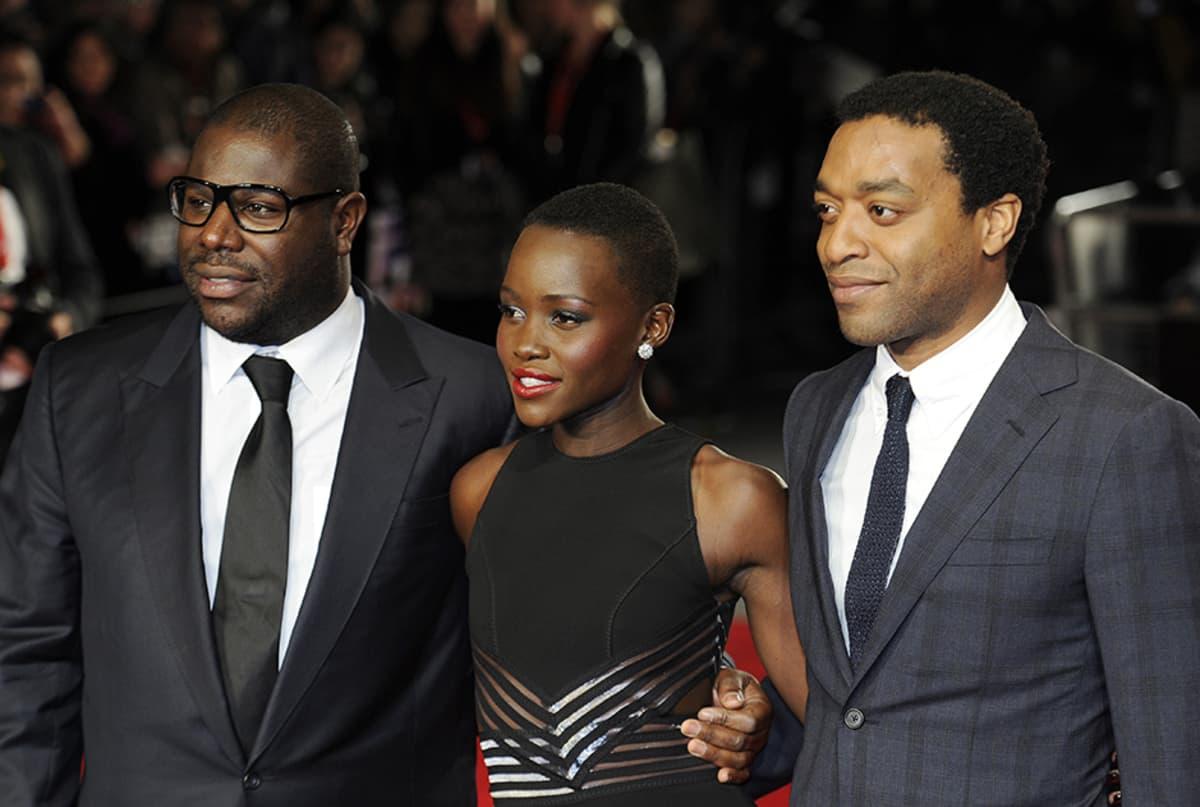 """""""12 Years a Slave""""-elokuvan ohjaaja Steve McQueen (vas.) sekä näyttelijät Lupita Nyong´o ja Chiwetel Ejiofor elokuvan ensi-illassa Lontoossa lokakuussa 2013."""