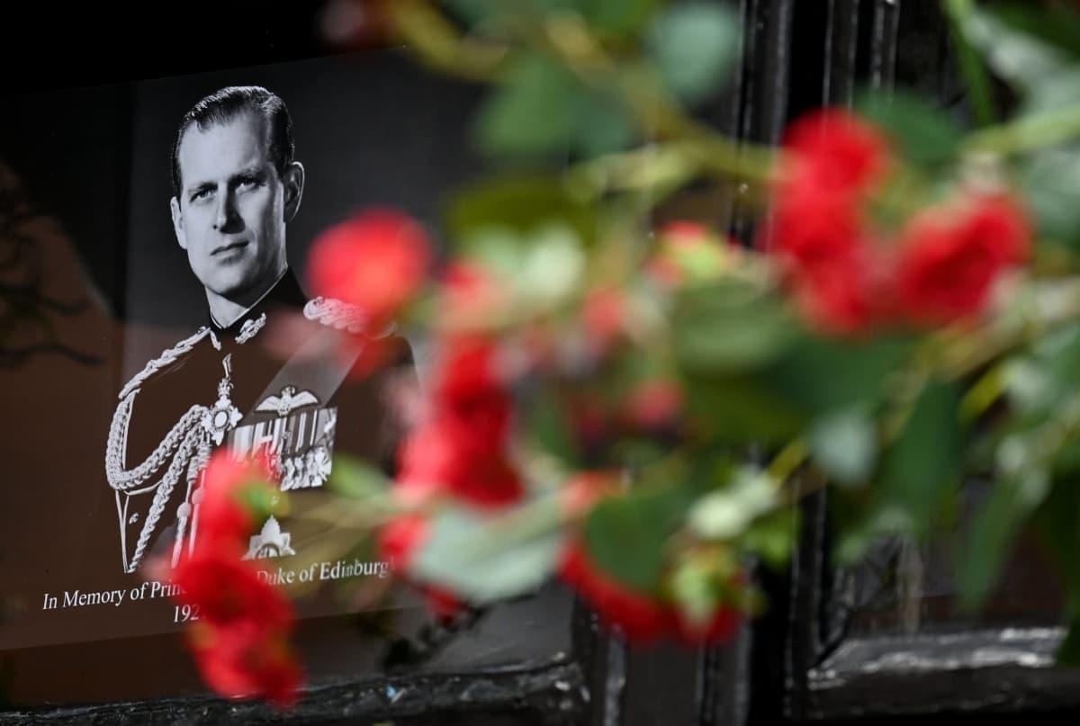 Viranomaiset ovat pyytäneet, että ihmiset eivät kerääntyisi Windsorin linnan ja Buckinghamin palatsin edustalle koronapandemian takia. Kuvassa näkyy Windsorin linnan edustalle laskettuja kukkia ja prinssi Philipin muistokuva.