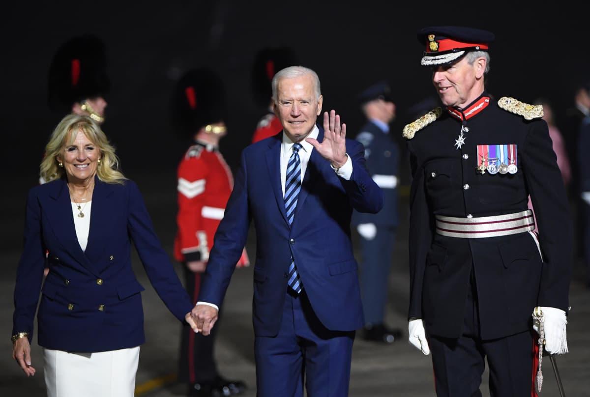 Joe Biden vilkuttaa kuvaajille ja pitää Jill Bidenia kädestä.