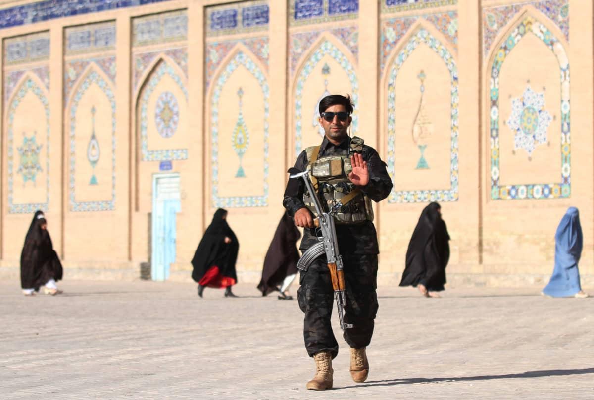 Vartija seisoo aseen kanssa moskeijan edessä.