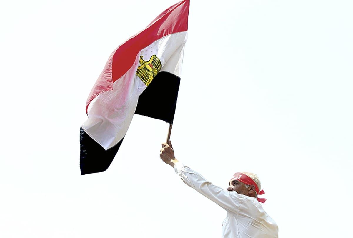 Mies kannattelee Egyptin lippua.