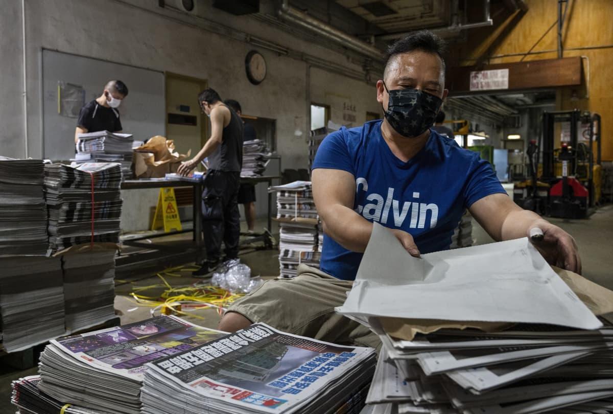 Työntekijät niputtavat Apple Daily -lehden numeroita.