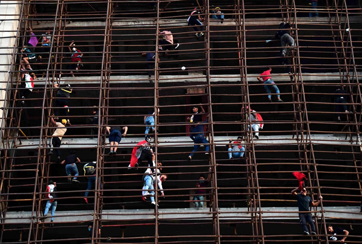 Mielenosoittajat roikkuvat rakennuksen rakenteista.