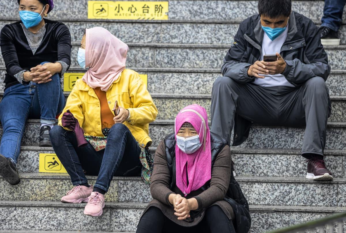 Uiguureja hengitysmaskit päällään Guangzhoun päärautatieaseman lähellä 12. helmikuuta 2020.