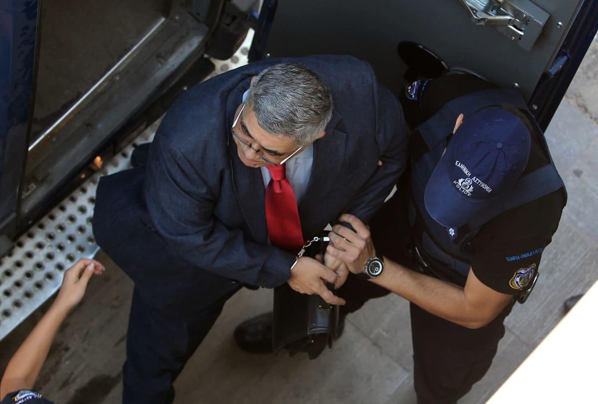 Nikos Michaloliakos käsiraudoissa poliisi vierellään. Heidät on kuvatt ylhäältäpäin.