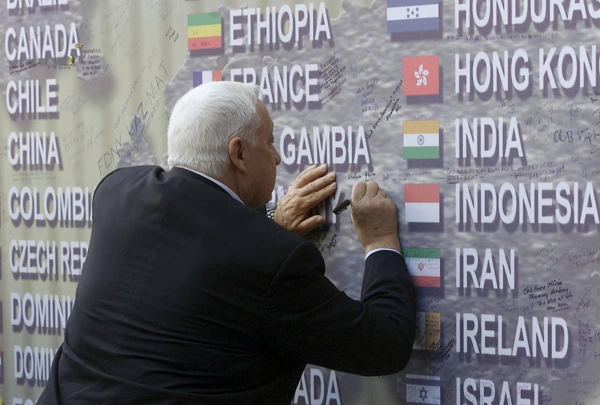 Israelin pääministeri Ariel Sharon kirjoittaa viestiään Saksan lipun perään WTC-iskun muistomerkillä New Yorkissa 30. marraskuuta 2001.